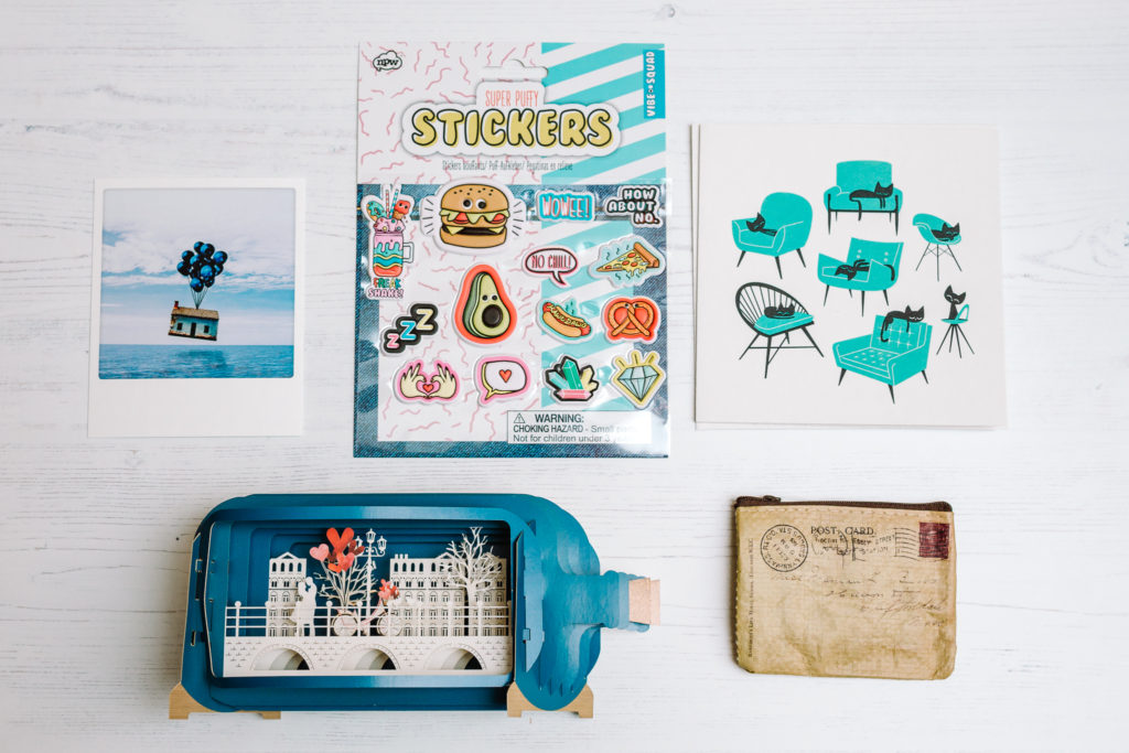 Stationery subscription box contents January 2019, showing a flatlay of a polaroid postcard, puffy stickers, a square card with black cats on turquoise chairs, a pop up bottle shaped card and a postcard-shaped purse | inkdrops.co.uk