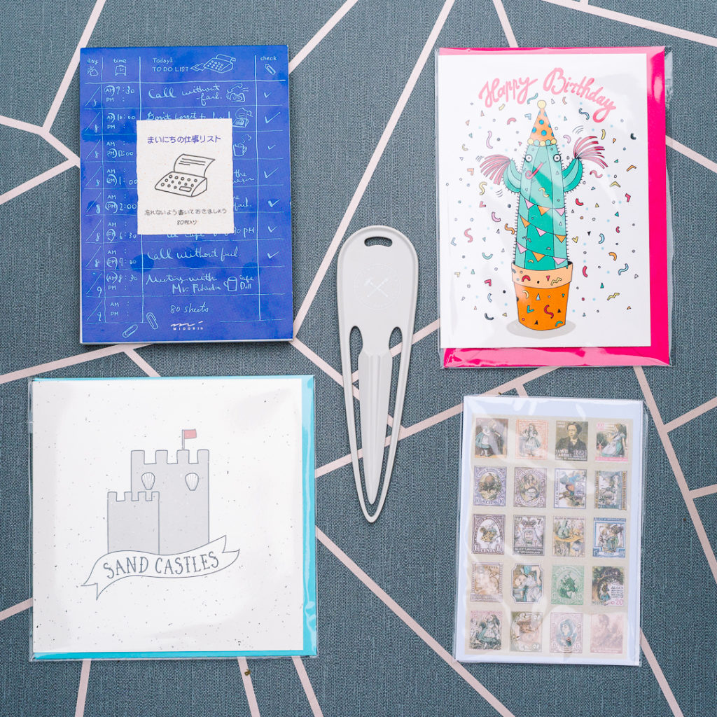 July 2019 stationery subscription box, showing a to do list pad, a letter opener, a cactus birthday card, some Alice in wonderland stickers and a sandcastle card - inkdrops.co.uk